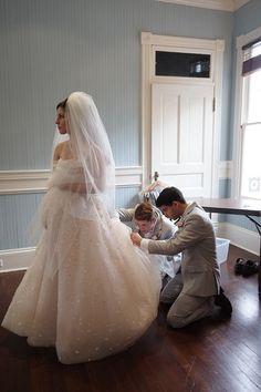 Los caballeros de honor ayudan a la novia con su vestido de Christos Peony.    6ad32bd17c4