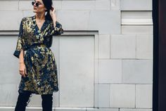 Anisa Sojka styles gold jacquard Munthe wrap dress | Black over the knew thigh-high boots | Gold and silver dainty stackable Lucky Eyes London necklaces | Round classic Rayban sunglasses with gold frame | Brunette shoulder length hair tied in a low ponytail | Fashion blogger street style shot in London by Moeez Ali