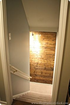 Do some sort of wall treatment on the wall at the bottom of the basement stairs to create interest. DIY wood planked wall dark stain