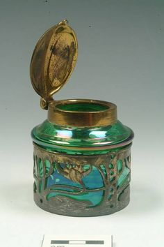 Green glass ink well with art nouveau design in a copper alloy band around the rim. It has a hinged copper alloy lid. (I was told that the lily blossom motif around the bottom is really made of steel)