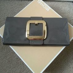 Michael Kors Envelope Clutch Beautiful gray patent leather envelope clutch with a large gold engraved buckle.  Snap Closure Several credit card slots One open pocket MICHAEL Michael Kors Bags Clutches & Wristlets