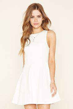 A sleeveless knit skater dress featuring a round neckline, a scoop back, and a flared skirt.