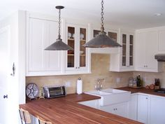 white painted maple cabinets, cherry butcher block countertops oiled with tung oil, Ikea double Domsjo farmhouse sink, peninsula,  integrated bosch dishwasher