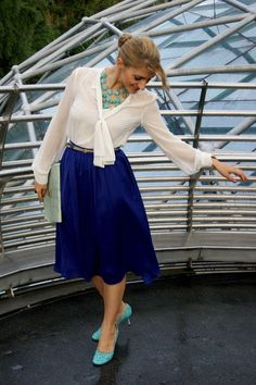 white tie blouse, belted blue skirt, statement necklace