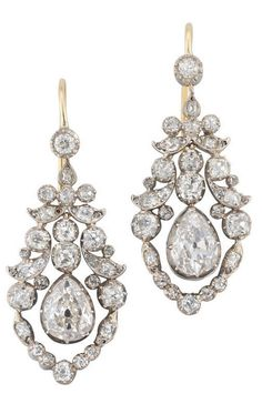 A pair of late Georgian open work diamond drop earrings, set with three graduating old brilliant-cut diamonds, the principle pear shaped diamond weighing approximately 3.50 carats the pair, suspended from two old brilliant-cut diamond within a diamond scroll design, all silver cut down collet to open yellow gold mounts with hook fittings, measuring approximately 4 cm in length, circa 1830.