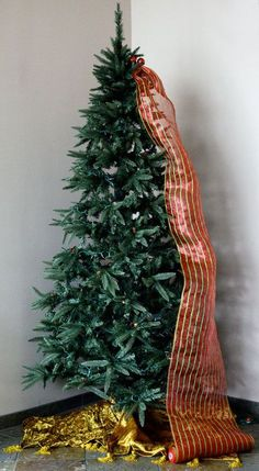 Christmas tree decorated with mesh ribbon and gold at the base