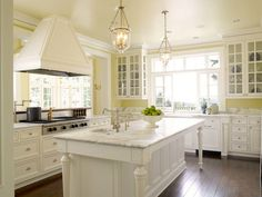 pretty pale yellow and white kitchen ~ love the glass lanterns and bright white island with turned legs and prep sink
