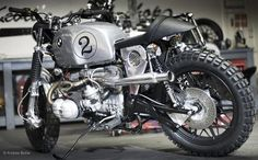 Kevils Sparky Beemer. Here's another fine scrambler boxer twin from the West Country's Kevils Speed Shop, this time given the moniker, Sparky. The build was commissioned by John in London, and is based on a 1980 BMW R100 featuring a chrome powder coated tank, custom high level stainless two into one exhaust, retro rocker covers, polished aluminium side panels, fully upholstered cafe seat and digital speedo.