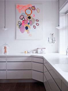 white kitchen and colourful picture