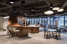 Workstations are minimized to provide room for collaborative booths, small and large huddle rooms, and standing height counters along the perimeter. Huddle rooms feature over-sized graphics of creative vanguards from Bob Dylan to Maya Angelou.