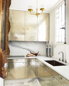 Metallic cabinets, marble countertops and backsplash, and gold light fixture in a glamorous kitchen