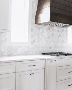 Year after year, one trend remains the same... You cannot go wrong with classic white kitchens featuring marble and wood accents! Design by @thedivinelivingspace. Photo by @kiley_marissa. Kitchen Hoods, Kitchen Backsplash, Kitchen Units, Hexagon Tiles, Mosaic Tiles, Honed Marble, Carrara, Kitchen Vignettes, Classic White Kitchen