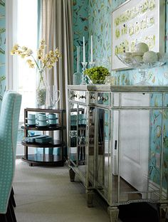 Gorgeous Dining Room with turquoise wallpaper, dining chairs, dishes and other accents.....and I LOVE the mirrored buffet!