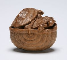 Two tortoises climbing out of a basket