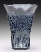 "R. LALIQUE IBIS VASE. R. Lalique clear glass vase is done in the Ibis pattern depicting Ibis birds standing among tall foliage. The deeply impressed pattern gives way to a clear, slightly flaring lip. The pattern is enhanced with a rich gray patination. Signed on the underside with engraved script ""R. Lalique France"". SIZE: 9″ t."