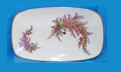 Gerold Porzellan plate tray with heather flowers platter Model series number is 7198 which were produced in the early 1970's. Porcelain plate tray with pink-purple spray of heather flowers and blue gray bow. The plate has silver trim. The tray has a slightly curved upwards.It measures 12 in long by 7 1/4 in wide and is 1 to 1 1/2 in high. Hallmark on back is Gerold Porzellan Tettau Bavaria Made in West Germany which is post 1949 hallmark.