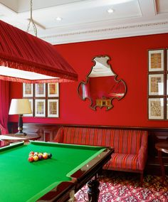 The billiard room walls are covered in red carriage cloth with matching curtains. The Nina Campbell Chopin bench is covered in Nina Campbell red and purple Voluta Stripe velvet.