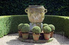 this large urn would make a great fountain ... surrounded by the clay pots filled with boxwood