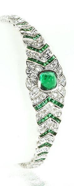 An Art Deco platinum, diamond and emerald bracelet. The bracelet centers on a sugar loaf emerald that has an approximate weight of 1.25 carats and is surrounded by round diamonds and calibre-cut emeralds tapering down the wrist in a chevron motif. The approximate total weight of the diamonds is 4.00 carats and the total weight of the calibre-cut emeralds is approximately 1.00 carat. Circa 1920.