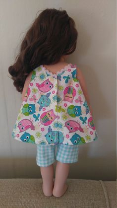 This adorable owl print top and shorts outfit is designed to fit any 18 inch doll. The outfit comes with cute teal plaid shorts with an elastic waistband. The top is a swing style and features a sweet little heart shaped pocket that matches the shorts and pretty pink trim along the neckline. The back closes with a Velcro closure making it easy for little hands to dress their dolls. This outfit is sure to be a hit this spring! This is a handmade item made of high-quality 100% cotton fabric in…