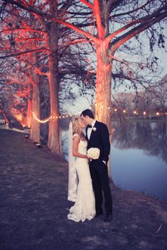 Uplighting on trees and strand lighting swagged between trees for outdoor wedding. Beautiful bride and groom. Wow Factors can create this look for your outdoor wedding!