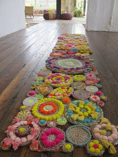 Handmade, DIY rope rug in super bright colors with pom poms.