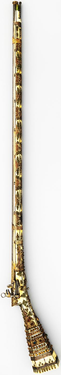 """Ottoman miquelet gun, late 18th c, steel, wood, ivory, brass, mother-of-pearl, paste jewels, Cal, .49 in. (12.45 mm), L, 60 3/4 in. (154.31 cm), Met Museum. The miquelet is an early, sturdy form of flintlock popular in the Ottoman Empire from the 17th to the early 20th c. Several elaborately decorated guns similar to this one are preserved in Istanbul, possibly made for the Ottoman Imperial guard. Lock inscribed: """"Muhammad Ayyubi"""", on the barrel: a Turkish test mark and an undecipherable…"""