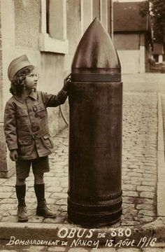 Little girl near an unexploded shell after a bombardment in Nancy, France, 1916.