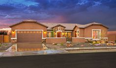 This ranch-style Reese home, available in Queen Creek, AZ, greets guests with a charming front courtyard. Stucco and stonework combine with bright white trim to create an inviting first impression. Built by Richmond American.
