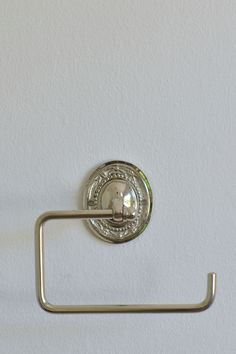 A wall mounted oval plaque with an attachment to hang a toilet roll from. Manufactured in India Made from silver plated brass Imported by Masquerade Toilet Roll Holder, Masquerade, Wall Mount, Hooks, Silver Plate, Door Handles, Plating, Brass, India