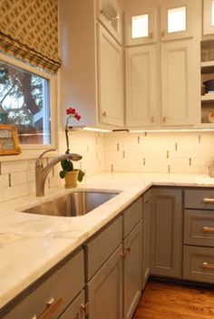 Grey lower cabinets, white countertop, white subway tile, white upper cabinets