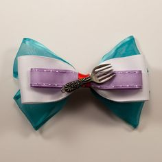 Princess Ariel Inspired Bow This bow, inspired by Princess Ariel, features a sheer blue ribbon that matches Ariel's formal dress and has accents of red for her hair. It also features a dinglehopper widget on the front just like the one Ariel uses to brush her hair. This bow is approximately 5 inches wide. Featuring a french barrette, this bow can be worn however you like in your hair.  Perfect for a day at the Disney Theme Parks!