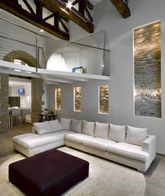 Living room with large white sectional couch high ceiling exposed beams and stone accent wall