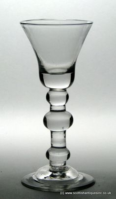 Baluster wine glass c1720 . The flared round funnel bowl has a solid section at the base. The stem is very well balanced with shoulder and basal ball knops with a larger ball knop set between http://www.scottishantiques.com/georgian-wine-glasses/baluster-stems/three-knop-stem#.VfxWoM6VK-4