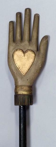 Odd Fellows Carved and Painted Wooden Heart and Hand Staff, Ohio, 19th century, depicting an open hand centered with a gilt heart raised on a wooden staff, painted off-white and red with gilt accents, the shaft painted black, ht. 73 3/4 in.    Note: The heart and hand symbols in Fraternal organization rituals are incentives to practice love and mercy.