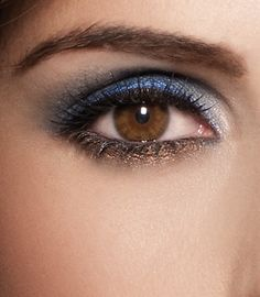 Blend the navy blue shade from lashline to crease. Layer the soft blue eye shadow over previously applied cream liner. Sweep the golden beige shade over brow bone. Line the upper lashline with the espresso shade. Smudge the cinnamon eye shadow shade into the lower lashline. Apply the icy pink eye shadow shade in corner of eye.