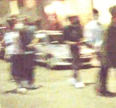 louis is holding harry's hand (around his shoulders) and then he sees the cameras and jams his hand into his pocket