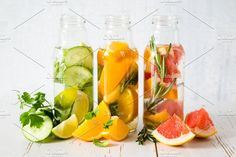 Selection of infused water in glass bottles, rustic wood background by NaumenkoOS on @creativemarket