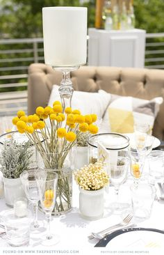 yellow rooftop wedding decor_004 arrangement of multiple small vases with assorted yellow and white flowers for a more eclectic feel