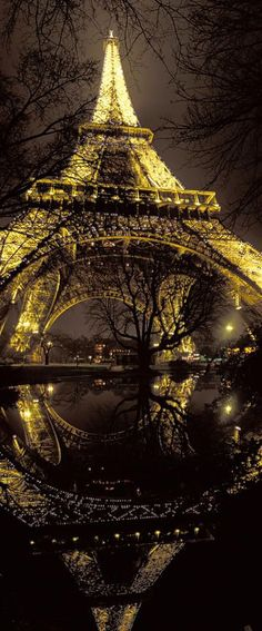 At the foot of Eiffel Tower at night, Paris, by Arnaud Frich