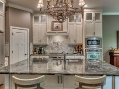 Traditional Kitchen with Crown molding, Glass panel, Complex granite counters, Flush, Stone Tile, Chandelier, Hardwood floors
