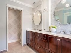This light gray and white bathroom features a cherry wood double vanity with a neutral countertop. Two globe pendant lights and a pair of circular mirrors are positioned in front of a gray mosaic backsplash, while a counter-to-ceiling storage tower provides space for stowing bathroom essentials.