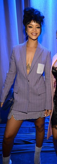 Rihanna wearing a Spring '15 Dior suit, showing off her chest tattoo with a plunging neckline.