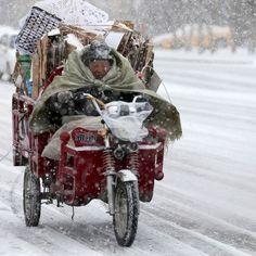 Un uomo guida la sua motocicletta ad Altay, nella provincia cinese dello Xinjiang, durante una forte nevicata