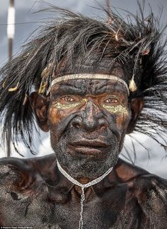 A Dani warrior with traditional headdress made through the use of the feathers of the bird of paradise. In Papua there are about 30 species of birds of paradise