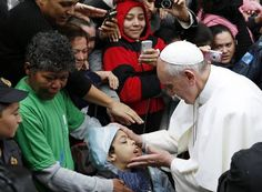 Pope Francis blesses a boy in the Varginha slum in Rio de Janeiro July 25, during his weeklong visit to Brazil for World Youth Day. (Catholic News Service photo/Paul Haring)