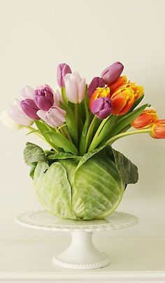 DIY Tulip Cabbage Arrangement:Why let another vase take up space in your home? With this arrangement, once you're finished with the cabbage vase, you can simply toss it in your compost pile.