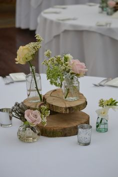 Vintage bottles on wooden Plinth with candles created by Eden Blooms at Northbrook Park
