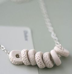 I love the different textures on the white porcelain disks. Simple white beads on a silver chain, but oh, the statement this would make.