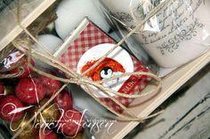 Små treskrin har blitt fylt med telys, fyrstikkeske, kubbelys og konfektbiter.         Kubbelys er dekorert med stempeltekst fra Kort og G...